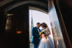 Happy newlyweds on the balcony of old gothic cathedral. View from doorway. With massive doors. High tower spire at background Stock Photo