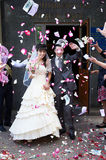 Happy newlyweds and flying petals Royalty Free Stock Photos