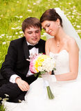 Happy newlyweds on grass in park Royalty Free Stock Images