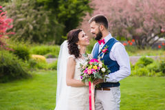 Happy newlyweds on the green lawn Stock Photos