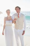 Happy newlyweds having champagne linking arms Royalty Free Stock Image