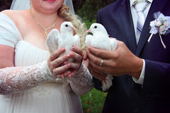 Happy newlyweds holding white doves. Close up with rose bouquet Royalty Free Stock Images