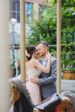 Happy newlyweds kiss near the carousel. Happy newlyweds kiss. Carousel Horses in foreground Royalty Free Stock Photography