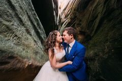 Happy newlyweds kissing at weathered dark rock cleft Stock Image