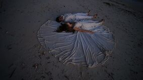 Happy newlyweds lie on the sand during sunset on the wedding dress of the bride. The original idea of filming. A stock footage
