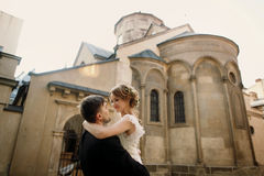Happy newlyweds portait - strong handsome groom lifting bride in Royalty Free Stock Image