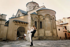 Happy newlyweds portait - strong handsome groom lifting bride in Royalty Free Stock Photos