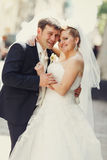 Happy newlyweds pose somewhere on the street. A Royalty Free Stock Photos