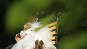 Happy newlyweds rests on bench in green sunny park. Groom lovingly touches his new wife's face stock footage