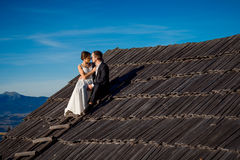 Happy newlyweds sitting on the roof of country house. Honeymoon in mountains Stock Photo