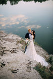 Happy newlyweds standing on the river bank Stock Photos