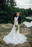 Happy newlyweds standing on the river bank Stock Images