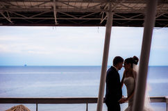 Happy newlyweds under the canopy by the seashore. Royalty Free Stock Image