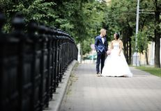 Happy newlyweds walking on a city street Royalty Free Stock Photo