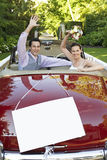 Happy newlyweds waving in convertible with blank sign in foreground Stock Image