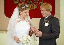 Happy newlyweds wear wedding ring Stock Photo
