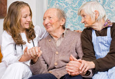 Happy news. Old couple and the young sweet doctor Stock Photos