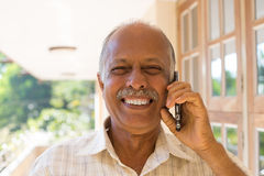 Happy news on phone. Closeup portrait, happy bald pensioner enjoying phone conversation. Call me on my cell phone, isolated outdoors outside background Stock Photo