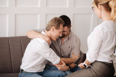 Happy nice gay couple hugging each other. Sexual minority. Happy delighted gay couple sitting together and hugging each other while visiting a therapist Royalty Free Stock Photo
