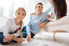Happy nice girl playing with a jigsaw puzzle Royalty Free Stock Photo