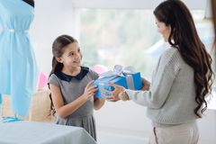 Happy nice girl receiving a birthday gift. Pleasant surprise. Happy nice positive girl holding a gift box and smiling while receiving a birthday present from her Stock Image
