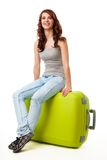 Happy nice girl sitting on the big green bag Stock Images