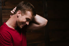 Happy nice guy in a red shirt. Is smiling on a dark wooden background Stock Images