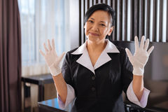 Happy nice hotel maid showing her hands in disposable gloves Royalty Free Stock Photos