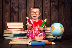 Happy a nice little girl with glasses and pencils against the background of books and a globe stock images