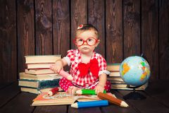 Happy a nice little girl with glasses and pencils against the background of books and a globe stock photo