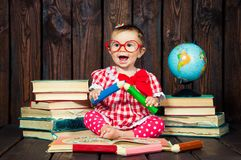 Happy a nice little girl with glasses and pencils against the background of books and a globe royalty free stock image