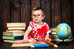 Happy a nice little girl with glasses and pencils against the background of books and a globe royalty free stock photos