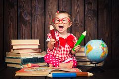 Happy a nice little girl with glasses and pencils against the background of books and a globe royalty free stock photo