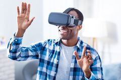 Happy nice man experiencing virtual reality. New dimension. Happy nice afro American man smiling and wearing 3d glasses while experiencing virtual reality Royalty Free Stock Images