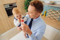 Happy nice man giving a bottle with milk to his baby daughter Royalty Free Stock Images