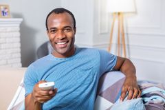 Happy nice man sitting in front of the TV screen. Leisure activity. Happy nice positive man sitting in front of the TV screen and holding remote control while Royalty Free Stock Images
