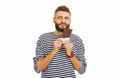 Happy nice man wanting to eat chocolate. Against the rules. Happy nice man holding a bar of chocolate while wanting to each it royalty free stock photos