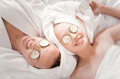 Happy nice mother and daughter doing a cucumber mask. Fresh look. Happy nice positive mother and daughter lying together and smiling while doing a cucumber mask stock photos