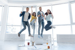 Happy nice people making a jump. We say yes. Happy nice positive people making a jump and laughing while celebrating their success Royalty Free Stock Photos