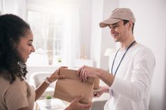 Happy nice person taking the bag. Food delivery. Happy nice person taking the bag while looking at the delivery man royalty free stock images