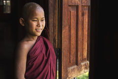 Happy Novice Buddhist Monk at Indein Village, Inle Lake, Myanmar. Happy novice Buddhist monk looking out the window at Indein village monastery in Inle Lake stock images