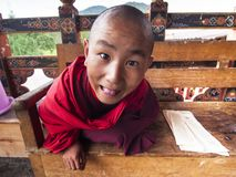 Happy novice monk of Punakha Dzong , Bhutan. A happy novice monk of Punakha Dzong , Bhutan , who make faces during his lesson . all sales revenue of this picture stock photos