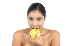 Happy nude brunette eating green apple Royalty Free Stock Image