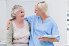 Happy nurse with arm around senior patient in clinic Royalty Free Stock Images