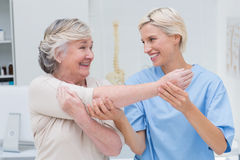 Happy nurse assisting patient in raising arm. Happy female nurse assisting senior patient in raising arm at clinic royalty free stock photos