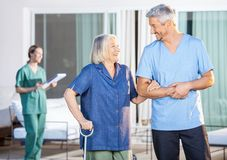 Happy Nurse Assisting Senior Woman To Walk. Happy male nurse assisting senior women to walk with caretaker in background at nursing home yard stock images