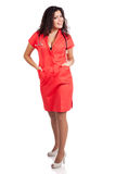 Happy nurse or doctor with hands in pockets. Beautiful happy young nurse or medical woman doctor with big breasts, wearing tangerine tango orange uniform dress Stock Photography