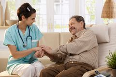 Happy nurse and elderly patient. Happy nurse holding hands of elderly patient sitting side by side at home, laughing Stock Photography
