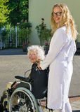 Happy Nurse and Elderly Patient Outside Hospital Stock Photo