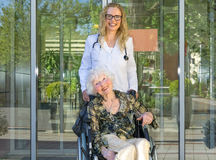 Happy Nurse and Elderly Patient Smiling at Camera. Happy Young Female Nurse and Elderly Woman Patient on Wheelchair Smiling at the Camera Against Hospital Glass Stock Photography